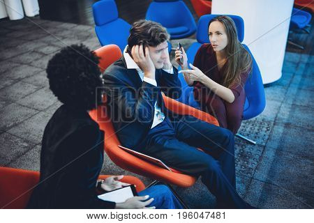 Two female business colleagues blaming their male co-worker while they three together having quarrel in office businessman sitting in central armchair is very stressed and closing his ears with hands