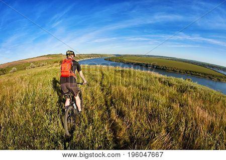 Adventure mountain biking on riverside. Traveler with backpack rides his bike in mountains.