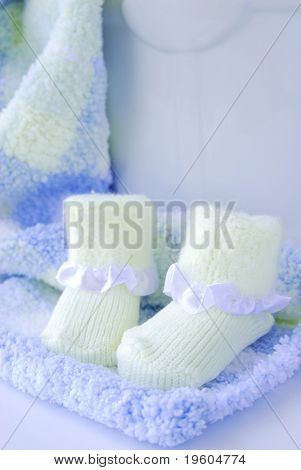 A still life of a baby blanket and baby socks