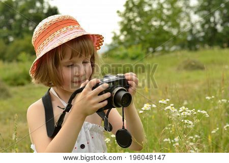 baby photographer (a little girl) with a camera on the background of  nature