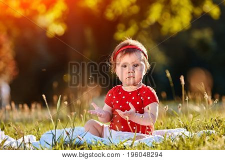 Close-up summer portrait of beautiful baby girl on the lawn in the park. Cute little girl in the white dress. Summer or spring season in the city park. Warm sunshiny day. Concept of the happy children.