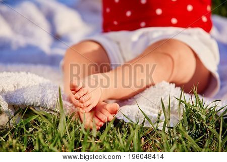 Close-up of the little baby legs on a green grass in the city park.