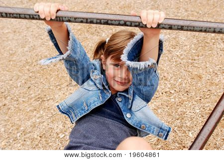 A cute young girl playing on the monkey bars