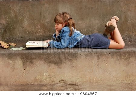 A cute young girl lying on a bench reading a book