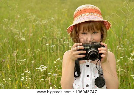 Portrait of a baby photographer (a little girl) with a camera on the background  of nature.