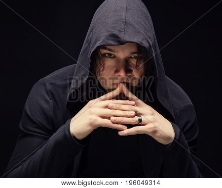 Puzzled young man in hood with hands on black background