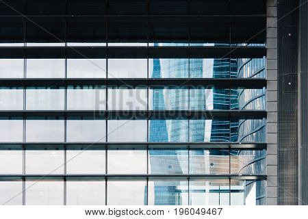 Madrid Spain - June 25 2017: Reflections on facade of skyscraper in business district. Cuatro Torres Business Area CTBA Four Towers Business Area a business district in Madrid against sky