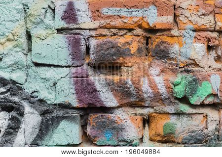 Dirty brick city wall, spattered with colorful spots of bright colors of aerosols. Stylish pattern, fashion colors, abstract background.