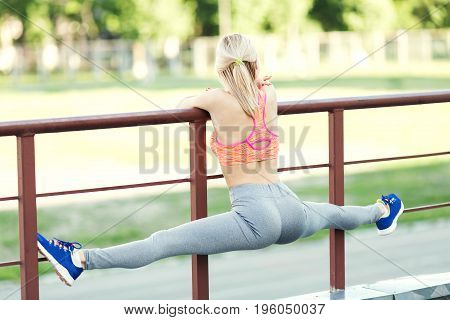 Young woman stretching before running outdoors. Fitness young woman stretching outdoors. A woman is sitting in a cross-twine