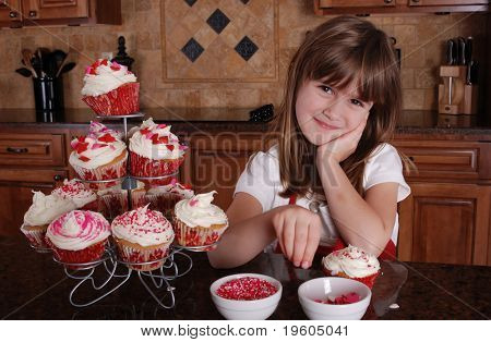 A cute young girl putting sprinkles on her cupcakes