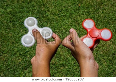 Asian boy holds a spinners fidget in his hands in Keningau,Sabah.The occupational therapist research has seen fidget spinners help kids to concentrate in the classroom