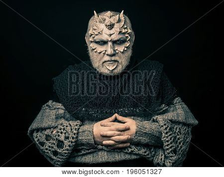 Demon With Folded Hands Isolated On Black