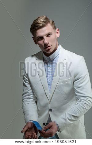 man or businessman in fashionable white jacket has blonde hair hold blue business card on grey background business ethic