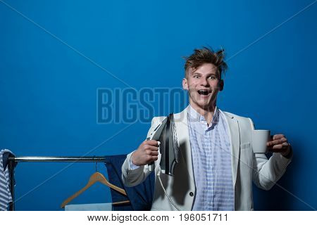 Guy smiling in wardrobe with morning cup. Everyday life and housework. Housekeeping and household. Man in jacket hold iron. Macho ironing clothes copy space