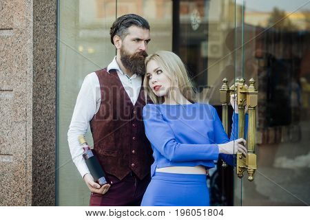 Hipster with bottle of wine hugging girl at glass door. Adorable woman in blue dress and brutal man outdoors on brick wall. Alcohol and convive. Couple in love. Unhealthy lifestyle. Bad habits