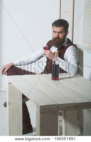 Hipster Drinking Red Wine With Bottle On Wooden Table