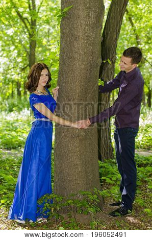 A young guy and a girl are standing on either side of the tree trunk and holding hands.