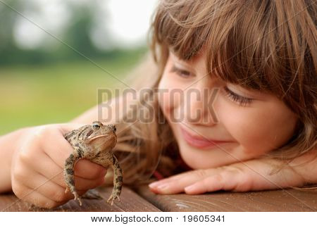 A cute young girl holding a toad