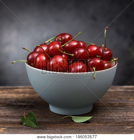 Ripe cherry in a bowl on a wooden board on a dark background