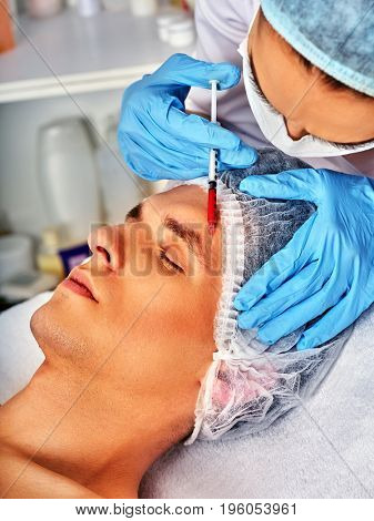 Filler injection for male face. Plastic facial surgery in beauty clinic. Man anti-aging therapy for complexion. Doctor in medical gloves with syringe forehead injects. Removal of skin defects. poster