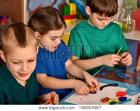 Plasticine modeling clay in children class. Teacher teaches kids together play dough and mold from plasticine in kindergarten or preschool. Group of four people. Diverse children's team.