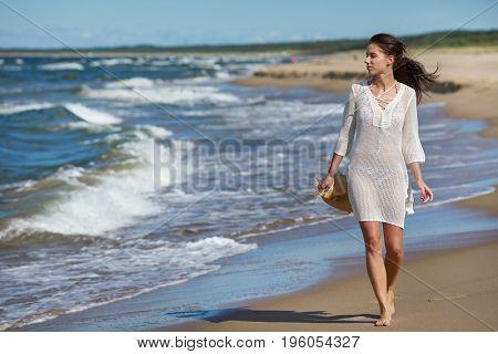 Young woman walking in water wearing white beach  dress