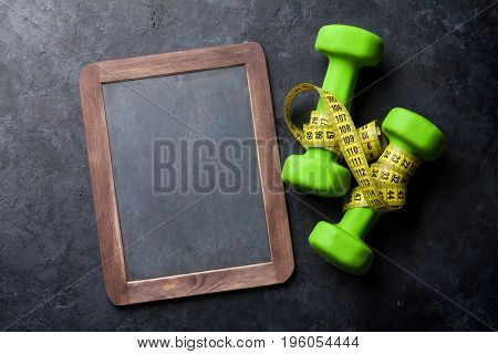 Dumbells and tape measure over stone table with chalkboard for copy space. Fitness and health