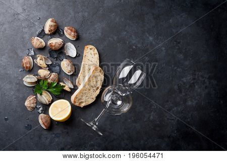 Fresh seafood and white wine on stone table. Scallops and wine glasses. Top view with copy space