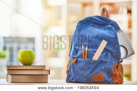 Back to school and happy time! Apple, pile of books and backpack on the desk at the elementary school.