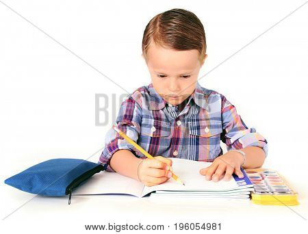 Five year old boy doing his homework. Studio isolated on white.