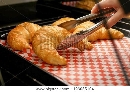 Woman buying croissants bread inside buy low foods store