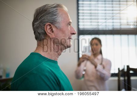 Side view of senior male patient with female therapist photographing against window at hospital ward