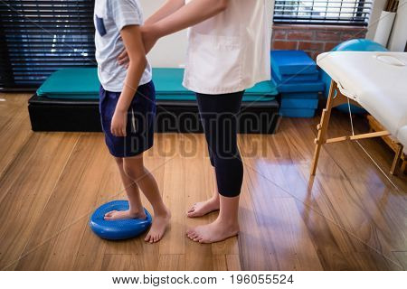 Low section female therapist holding boy standing on blue stress ball at hospital ward
