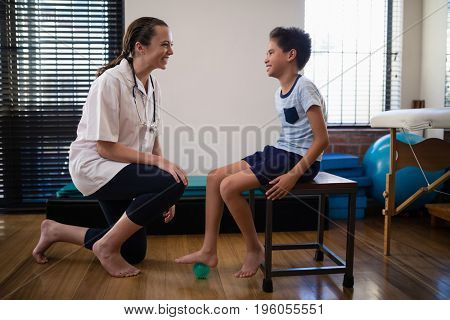 Smiling female therapist kneeling by boy stepping on stress ball at hospital ward