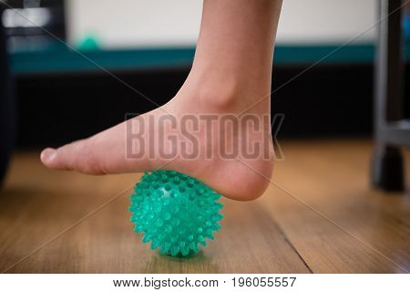 Low section of boy stepping on stress ball at hospital ward
