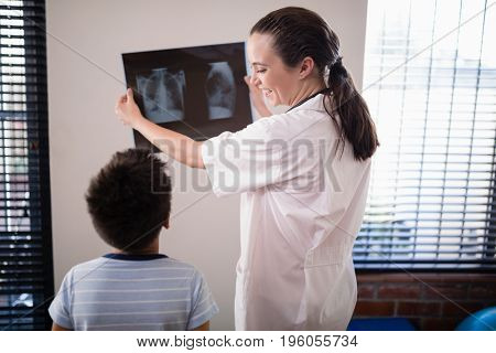 Smiling female doctor showing x-ray to boy against wall at hospital ward
