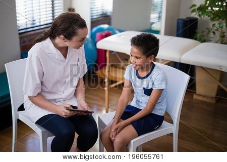 Female therapist and boy talking while sitting on chairs at hospital ward