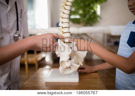 Midsection of female therapist and boy pointing at artificial spine on table in hospital ward