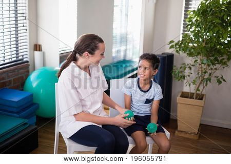 Smiling female therapist looking at boy holding stress balls while sitting on chairs in hospital ward