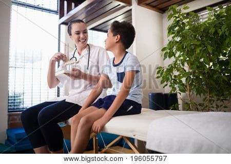 Smiling female therapist looking at boy with artificial bone while sitting on bed in hospital ward