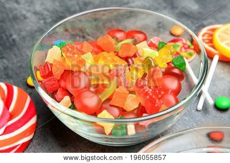 Bowl with delicious candies on grey background