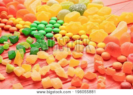 Composition of delicious candies on red background