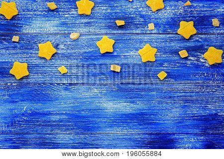 Composition of delicious star shaped jelly candies on blue wooden background