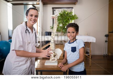 Portrait of smiling boy and female therapist standing with artificial spine on table at hospital ward