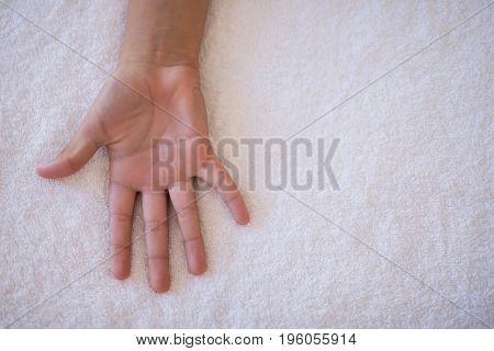 Overhead view of palm on white towel at hospital ward