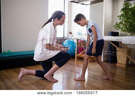 Boy showing knee to female therapist kneeling on hardwood floor at hospital ward