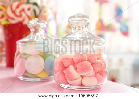 Tasty sweets in jars on table at candy shop