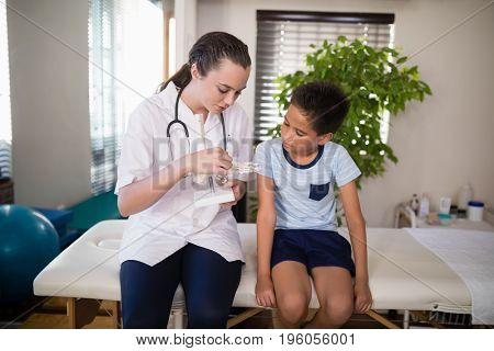 Young female therapist explaining boy with artificial bone while sitting on bed at hospital ward