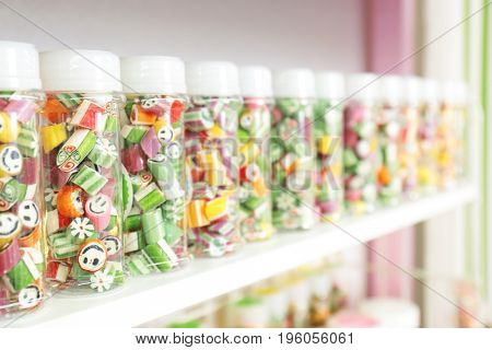 Jars with different candies on shelf at shop