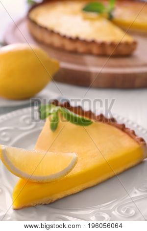Plate with delicious lemon pie on table, closeup